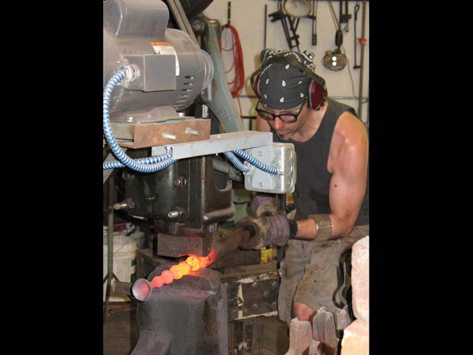 Chris Shea making a forged chair: Chris Shea at the power hammer