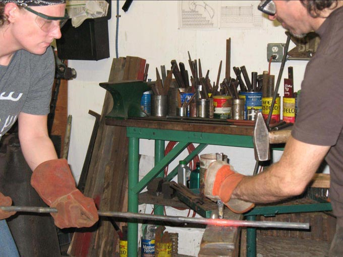 Chris Shea making a forged chair: Chiseling through hot steel